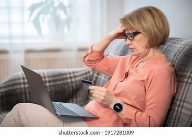 Nervous entsetzt verwirrten älteren Senioren Rentner, betonte besorgt, traurig frustrierte Dame Probleme mit dem Bezahlen, Online-Kauf, Zahlungen mit Kreditkarte blockiert Bankkarte, Laptop. Internetbetrug