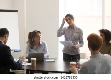 Nervous indian female worker presenter speaker feels embarrassed and shy stands in front of multi-ethnic colleagues clients at conference business meeting, timid stressed not prepared employee concept