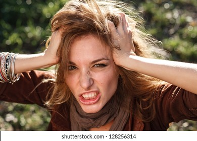 nervous mad woman with messy hairstyle closeup looking at camera outdoor