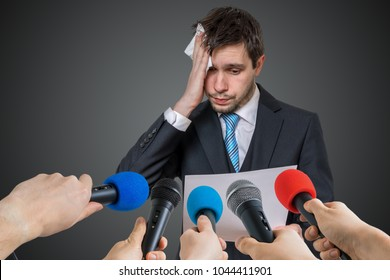 Nervous man is afraid of public speech and sweating. Many microphones in front.