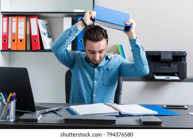 nervous manager throws a desk with a file with documents - nerves in office work