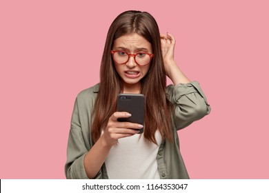 Nervous puzzled woman scratches head in bewilderment, reads bad news at internet, uses modern cell phone, wears fashionable clothes, worries aboutt something, stands in studio against pink wall