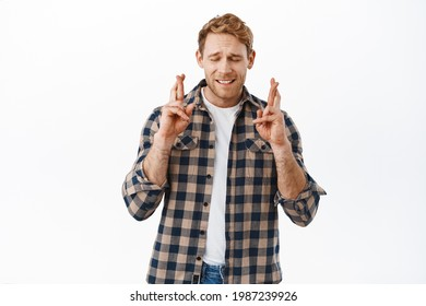 Nervous redhead guy begging god, cross fingers for good luck, making wish or pleading, waiting for news, anticipating positive results, standing hopeful against white background