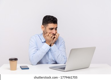 Nervous scared man employee sitting office workplace, looking worried anxious at laptop screen and biting nails, panicking of deadline, troubles at work. studio shot isolated on white background