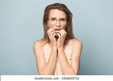 Nervous scared woman in glasses biting nails, feeling fear, stressed attractive female student, businesswoman thinking about problem, anxious, looking at camera, isolated on studio background