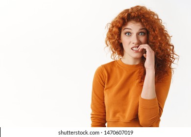 Nervous silly redhead cute woman with curly hair biting fingernails awkward situation, feeling guilt making small mistake report, look concerned and distressed, small panic standing white background