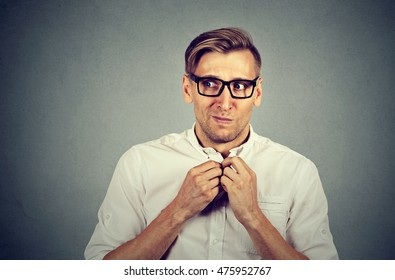 Nervous stressed young man student feels awkward looking away sideway anxiously craving something isolated gray wall background. Human emotion face expression feeling body language