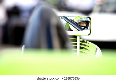 The nervous, tencely concentrated look in the eyes of a race car driver in his car on the starting grid of a race track, reflected in the side mirror of his vehicle.