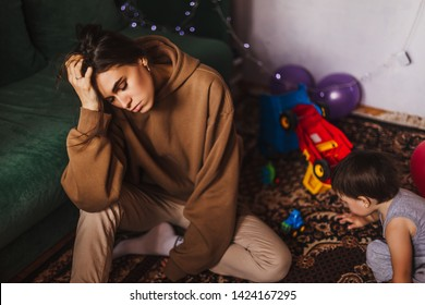 A nervous woman in a panic yells holding her head. The girl was tired of mess at home and active little noisy baby. Young tired girl surprised of toys quantity. Emotional burnout.