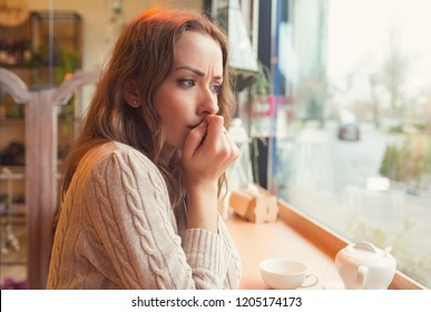 Nervous worried young woman biting nails and looking away sitting alone in a coffee shop