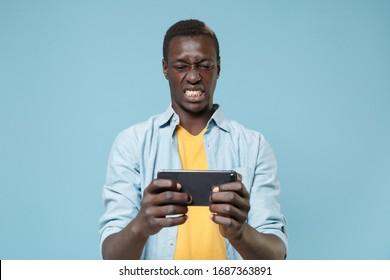 Nervous young african american man guy in casual shirt, yellow t-shirt posing isolated on blue wall background in studio. People lifestyle concept. Mock up copy space. Play game with mobile phone