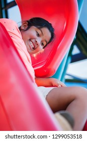 Nervous young girl with and excited facial expression that is holding on to a playground slide before letting go.