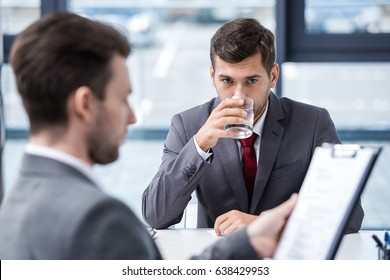 Nervous young man drinking water from glass during job interview, business concept