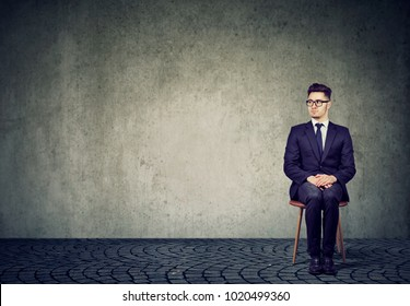 Nervous young man in suit sitting on chair expecting interview session in anxiety.
