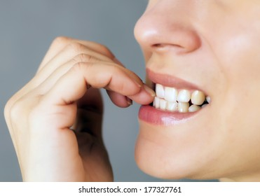 nervous young woman biting her nails on gray background