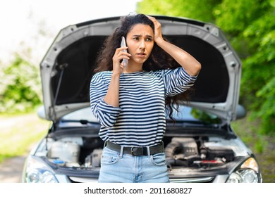 Nervous young woman standing by open car hood and calling to auto service, got broken at highway on a way to countryside. Female drive having phone conversation with friends, asking for help with auto