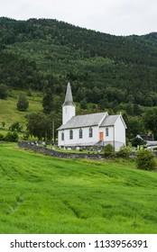 Nes kyrkje, Commune Luster, Norway. White wooden church, Green grass on a meadow