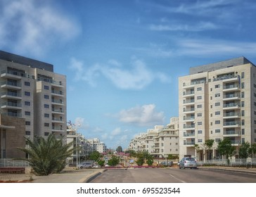 Nes Ziona, Israel-March 20, 2016: Front view of two modern 8 story residential condominiums are located on both sides of the beginning of Khoshen street. Wide urban road and blue sky. Horizontal shot