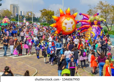 Nesher, Israel - March 22, 2019: People, some in costumes, celebrate the Jewish holyday of Purim in the Adloyada parade, in Nesher, Israel