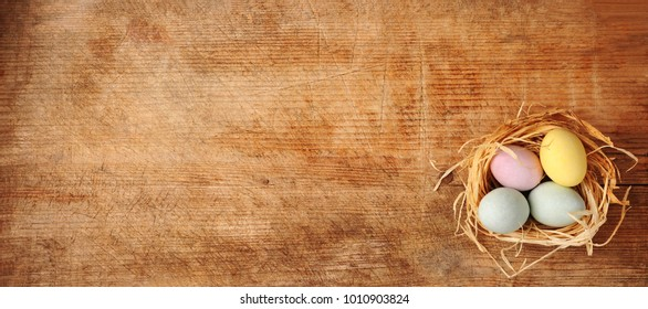 nest with Easter eggs over wooden background