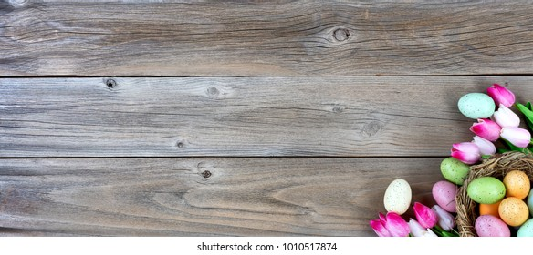 Nest filled with colorful eggs and pink tulips in lower right corner on weathered wooden boards for Easter background