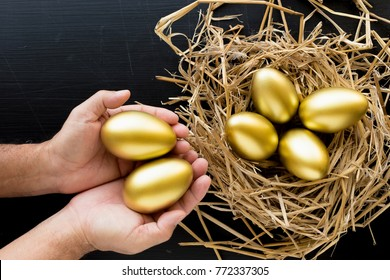 Nest Full Of Golden Eggs, Man holding a golden egg on black background. Financial success.