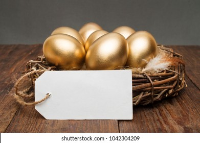 Nest with golden eggs with a tag and place for text on a wooden background. The concept of successful retirement.