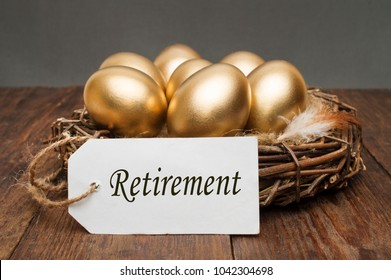 Nest with golden eggs with a tag and a word retirement on a wooden background. The concept of successful retirement.