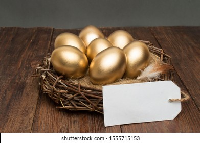 Nest with golden eggs with a tag and a word retirement on a wooden background. The concept of successful retirement