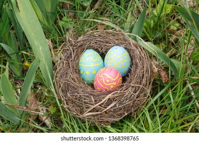 Nest with milk chocolate eggs wrapped in colored paper for Easter