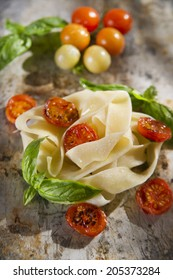 Nest of pappardelle pasta with tomato and basil