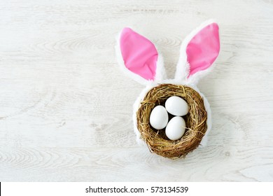 A nest with three white Easter eggs and bunny ears at home on Easter day. Celebrating Easter at spring. Painting eggs.