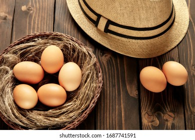 Nest in wicker basket with chicken eggs on a wooden table.