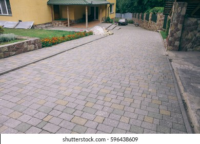 Nested pavers of various colors, around the grass is green, chic garden luxury courtyard, with the car