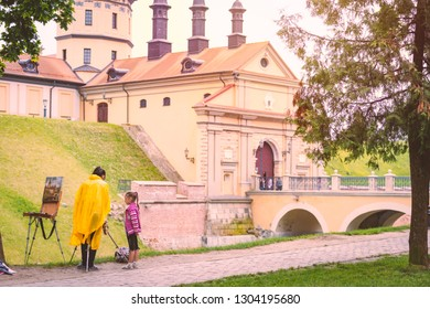 NESVIZH, BELARUS - JUNE 12, 2014: Old medieval castle in Nesvizh, Belarus, Europe. Young woman and girl with castle painting.