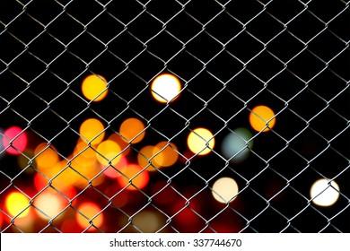 net fence on blur bokeh from traffic light background