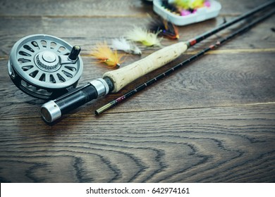Net, fishing rod, set by river for fly fishing on an old wooden table