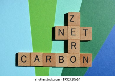Net, Zero, Carbon, words in wooden alphabet letters isolated on blue and green background