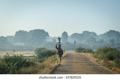 Netarhat, Jharkhand,India. December 09, 2016. An unidentified village woman is carrying home utensils after washing .