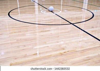 Netball Ball. An eye level long shot of a Netball Ball placed in the centre circle on an indoor Netball Court which is made of wooden floorboards.