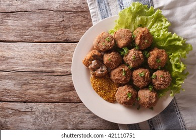 Netherlandish cuisine: meat balls Bitterballen and mustard close up on a plate on the table. Horizontal view from above