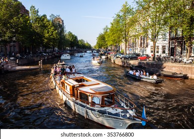 NETHERLANDS, AMSTERDAM - AUGUST 22, 2015: Veiw on the bridge through the river channel with boat, typical picture of canals in Amsterdam.