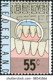 NETHERLANDS - CIRCA 1977: A stamp printed in the Netherlands, is dedicated to the 100th anniversary of the teaching of dentists, is shown Teeth, Mirror of Dentist, circa 1977