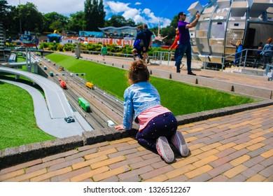 Netherlands. Den Haag. Miniature park Madurodam.July 2016. Selective focus.Girl look down on the miniature road in Madurodam park open air museum