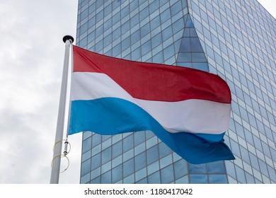 Netherlands flag. Dutch flag on a pole waving, modern office building background
