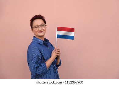 Netherlands flag. Woman holding the Netherlands Holland flag. Nice portrait of middle aged lady 40 50 years old with a national Dutch flag over pink wall background.