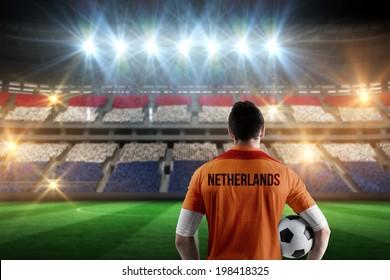 Netherlands football player holding ball against stadium full of netherlands football fans
