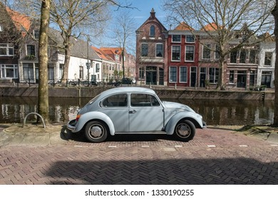 Netherlands, Gouda, 2017, An old volkswagen beetle, parked along the side of a canal or grachten. In the background the typical architecture of the city can be seen