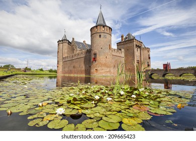 Netherlands, Muiden - June 23 2014: Muiderslot castle with pond and and water lilies on the foreground