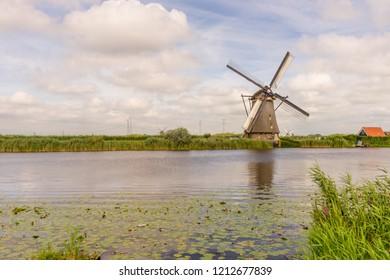 Netherlands, Rotterdam, Kinderdijk, heritage windmill above lush green grass along a canal